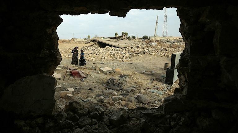 En familj står i ruinerna av byn Barzan på Ninevehslätten.