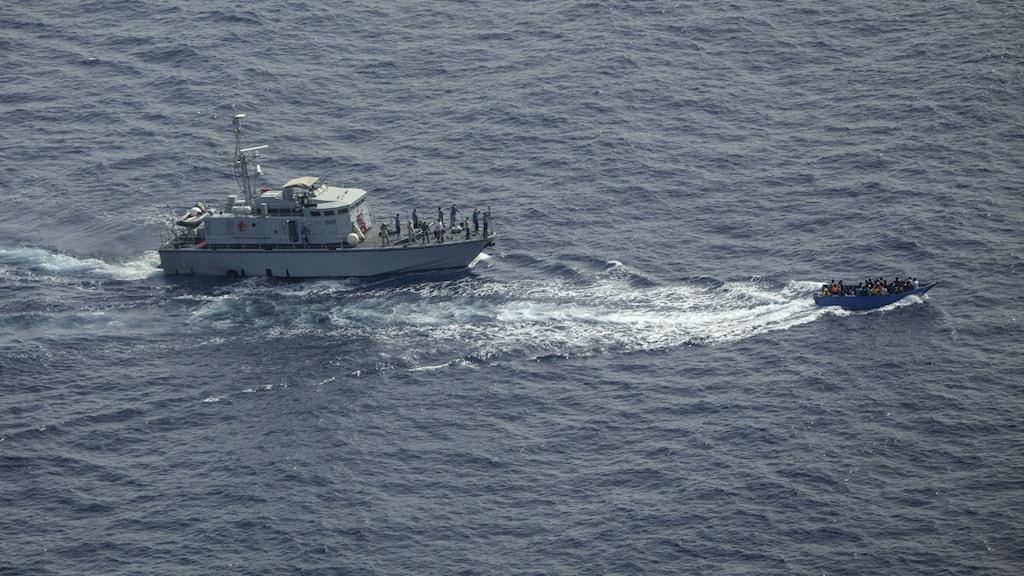 Kustbevakningsfartyg förföljer mindre överlastad båt.