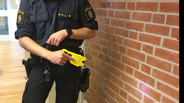 Bild på polisman med elchocksvapen.