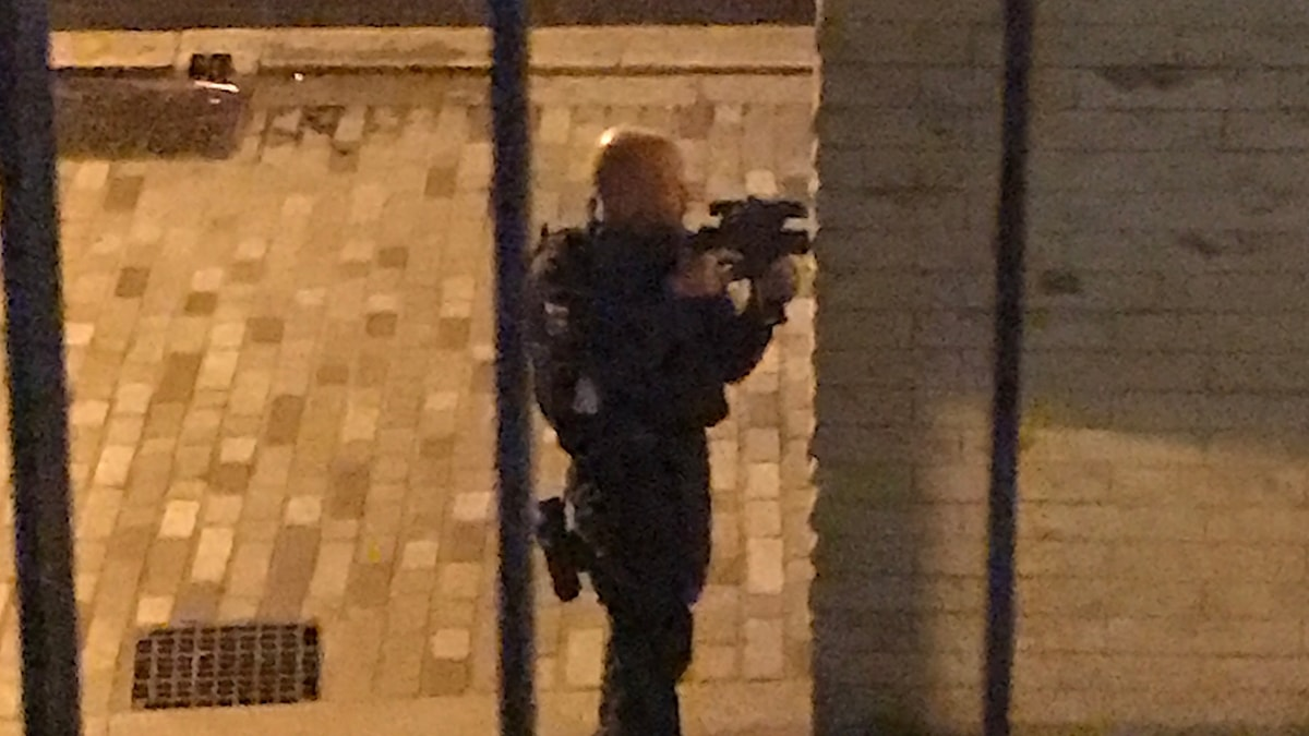 En beväpnad polis står utanför ett hus och siktar med sitt vapen.