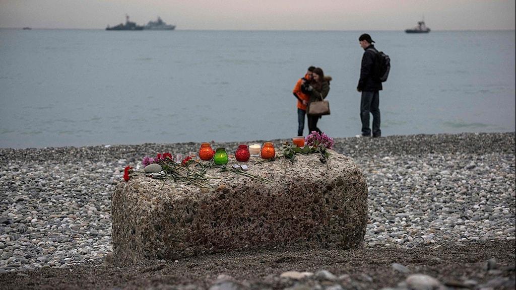 en sten med blommor på, i bakgrunden står tre personer och på havet syns två båtar
