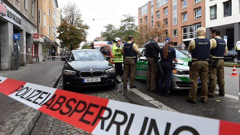Poliser står vid en bil bakom ett avspärrningsband.