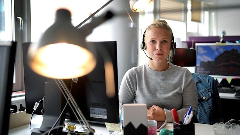 Kuratorn Catarina Nylund sitter framför datorn med ett headset.