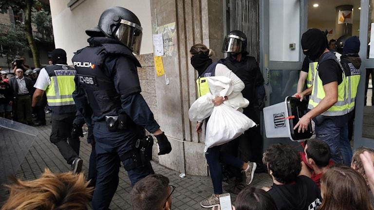 Spansk polis beslagtar valurnor från en vallokal i Barcelona strax efter att omröstningen börjat 09:00 på morgonen.