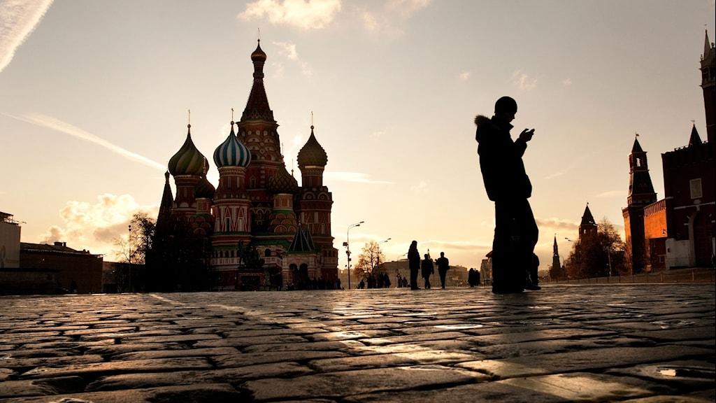 En person kollar ner i sin mobil på ett torg i Moskva