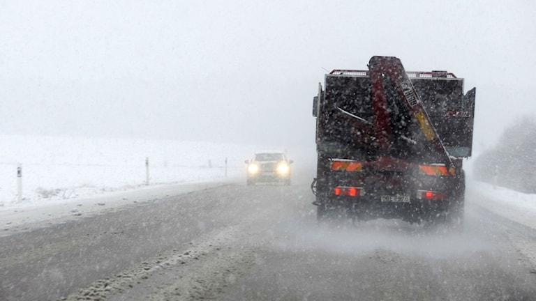 En bil och en lastbil möts på en väg i vinterväglag.