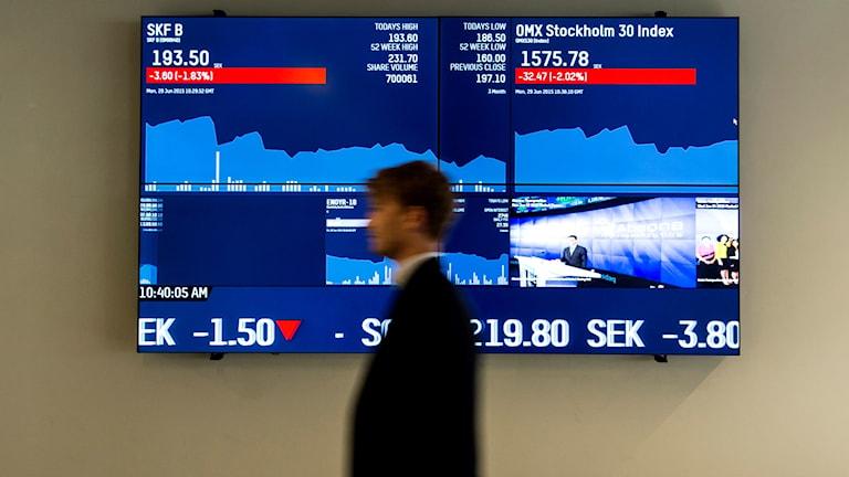 Stockholmsbörsen. En man går förbi en skärm.
