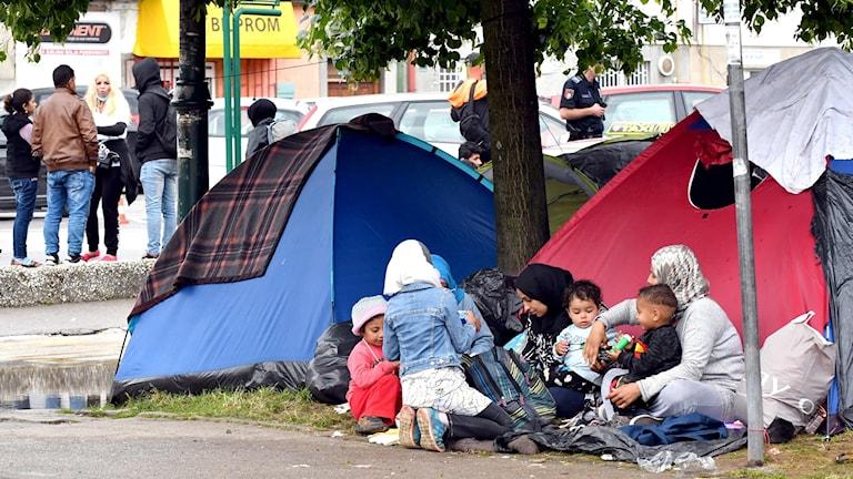 Familjer framför tält i stadsmiljö.