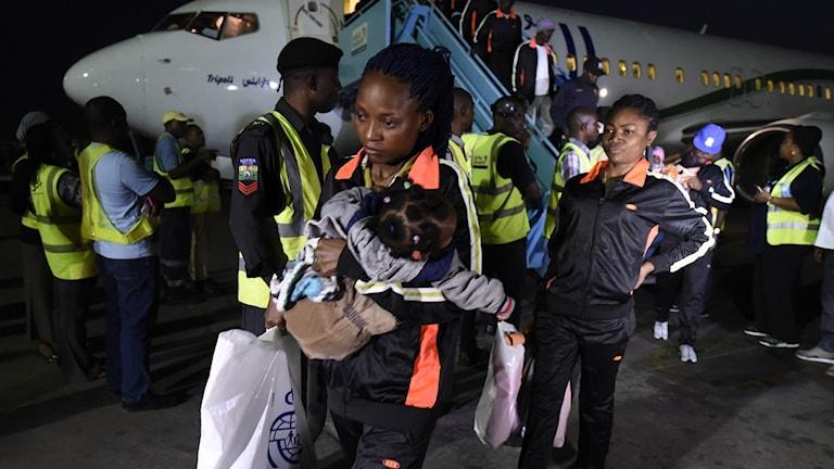 Kvinna bär ett barn efter att ha klivit av ett flygplan.