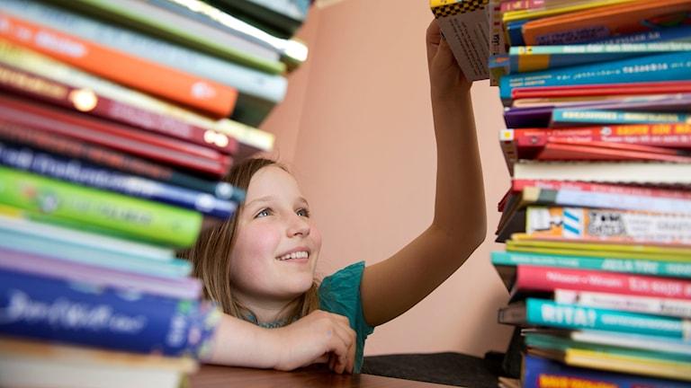 Flicka vid staplar av barnböcker