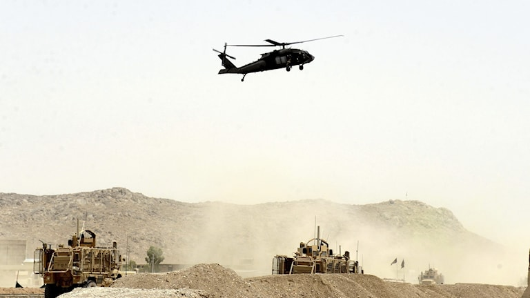 Helikopter över militärfordon i bergig öken.