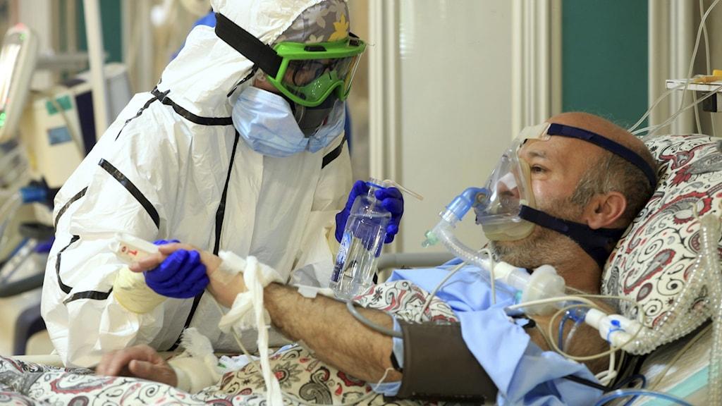 Man med andningsmask tas om hand av läkare i skyddskläder.