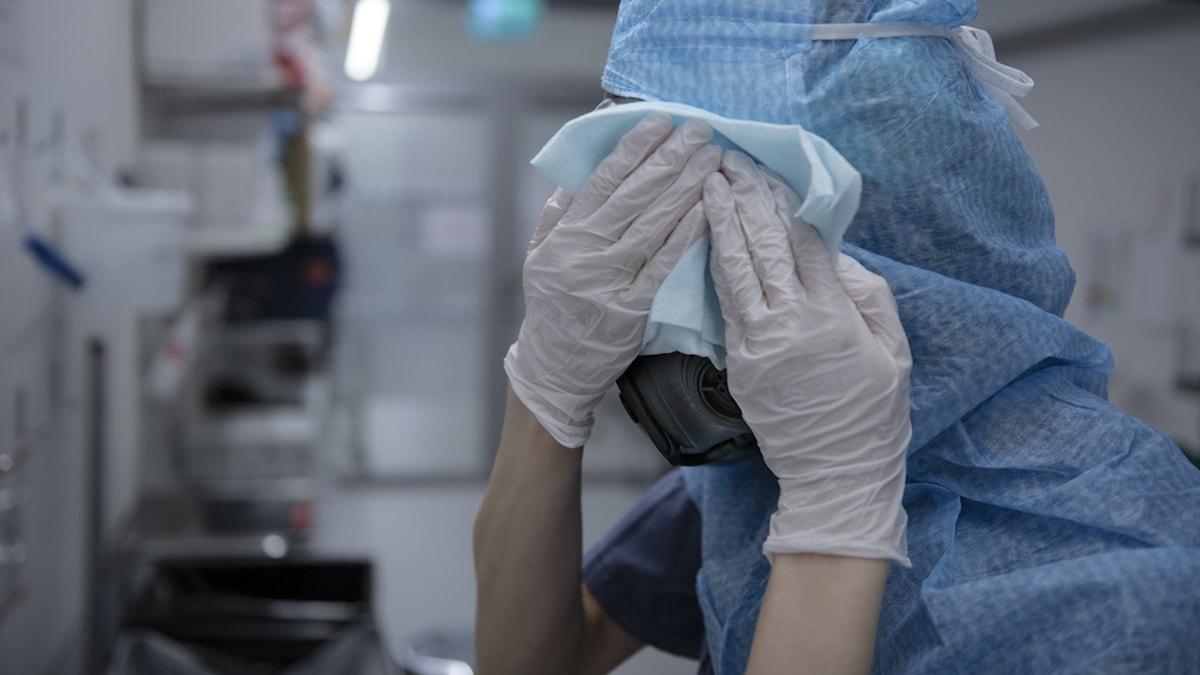 Sjuksköterska tvättar skyddsmask.
