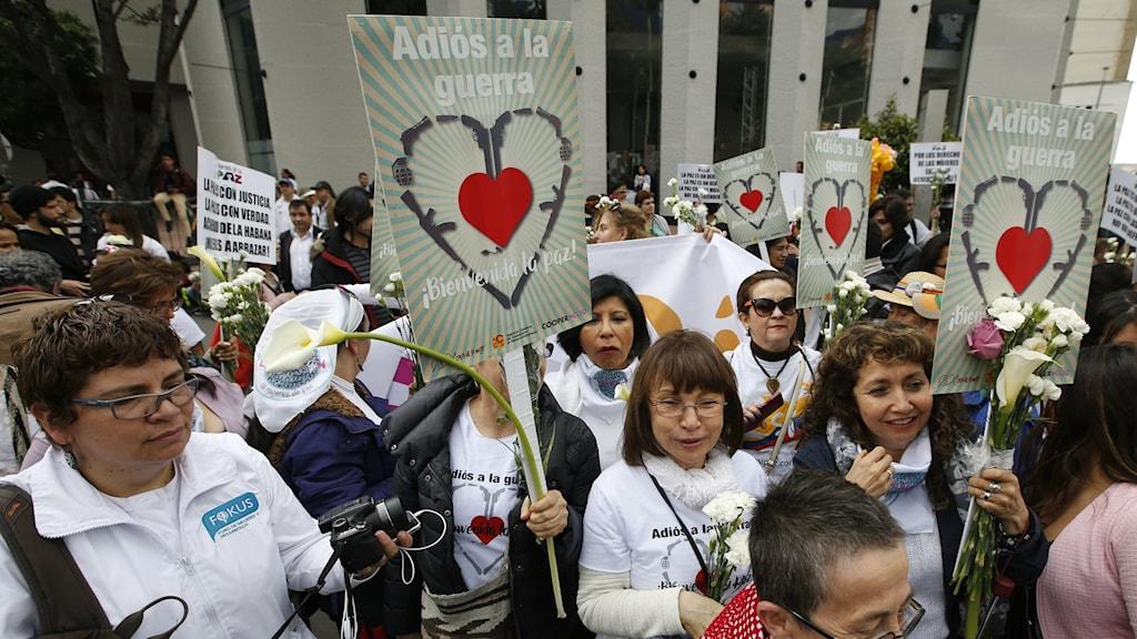 """Bilden visar en grupp kvinnor, de flesta i vitt i en fredsmarch i Bogotá, Colombia den 12 oktober 2016. De håller skyltar med hjärtsymboler med texten """"Adjö till kriget"""". Foto: Fernando Vergara/AP Photo/TT."""