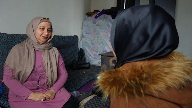 Kvinna sitter mitt emot en flicka som har ryggen mot kameran.