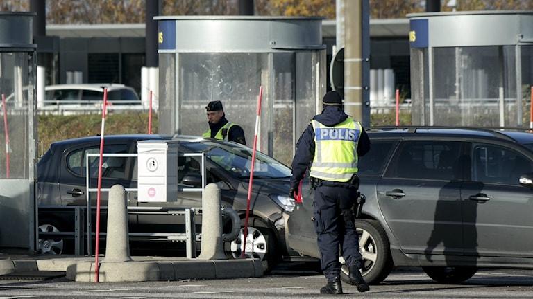 Bilden visar två poliser som gör gränskontroll vid betalstationen på Öresundsbron. Foto: Erland Vinberg/TT.