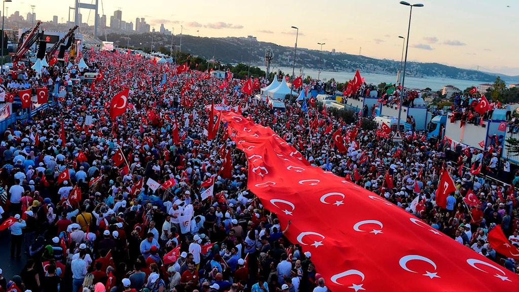En folkmassa står med en gigantisk turkisk flagga.
