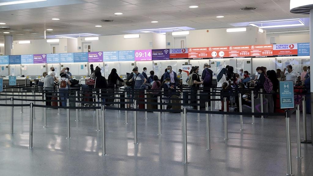 Kö vid incheckningsdiskar på Gatwick flygplats under coronatider.