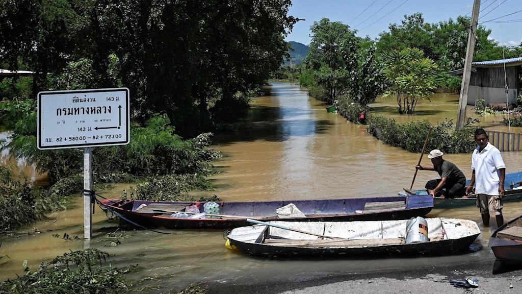 Båtar som flyter på vatten vid en vägskylt.