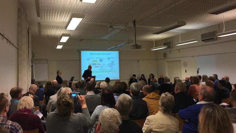 Bilden visar ett konferensrum fullt med folk. I fonden syns Leif Roth från Barsebäck Kraft AB framför en upplyst filmduk. På duken visas en bild över systemet i Sverige för att hantera kärnavfall.  Foto: Anna Bubenko/Sveriges Radio.