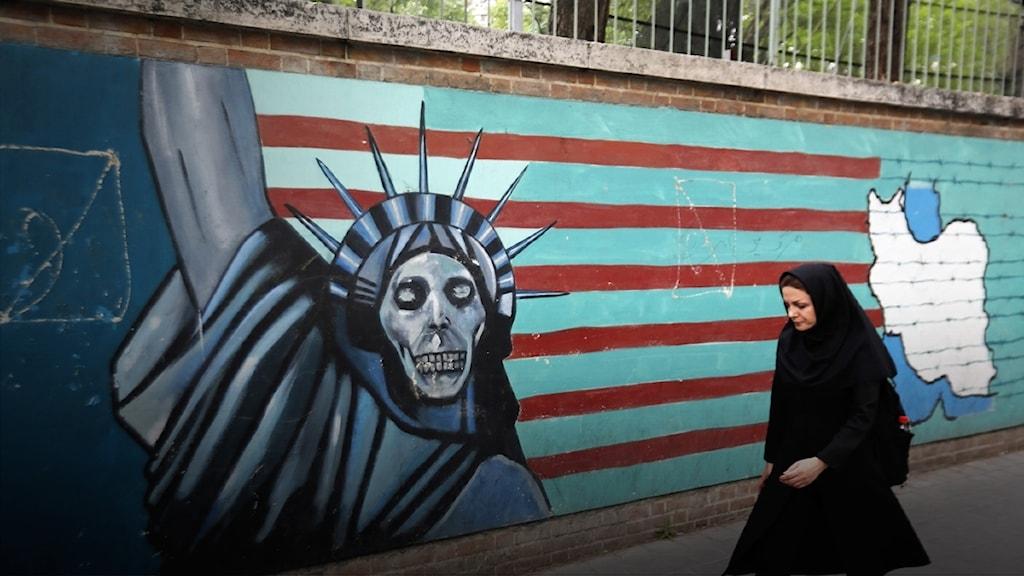En iransk kvinna promenerar förbi en väggmålning när den före detta amerikanska ambassaden I Teheran.