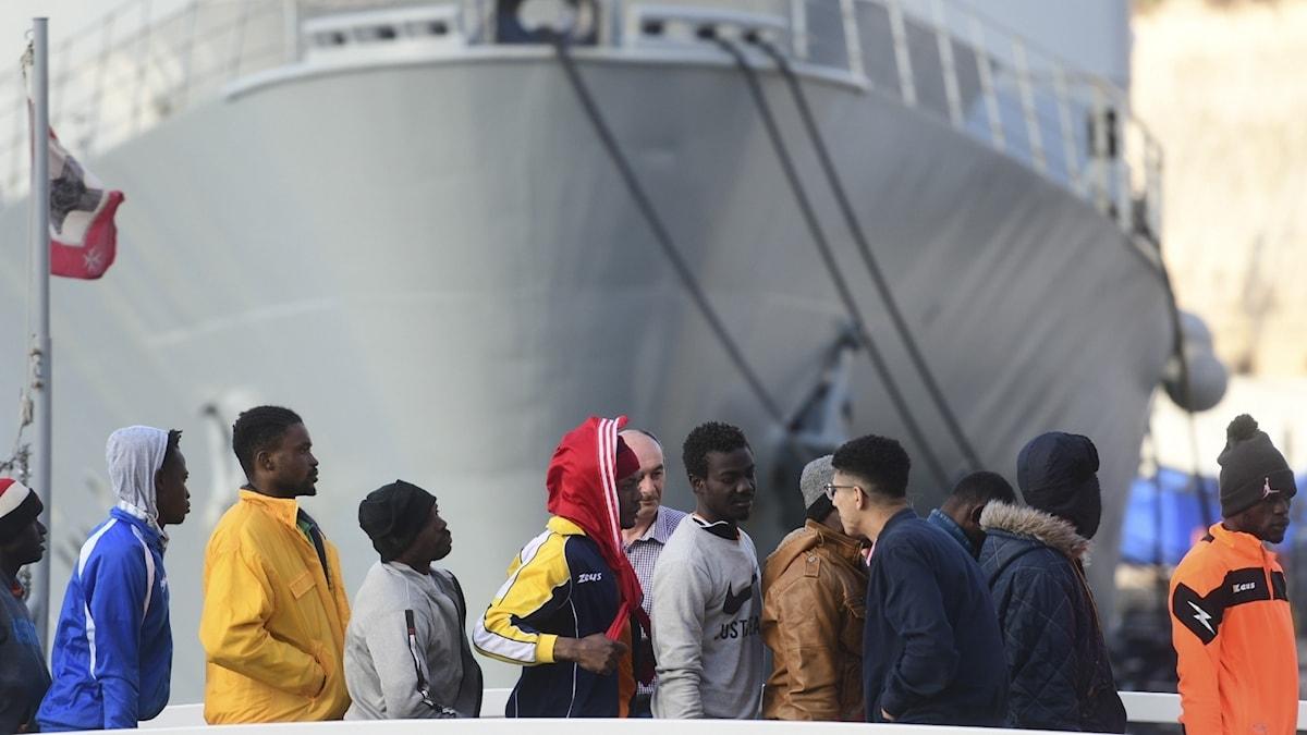 Migranter i en hamn.