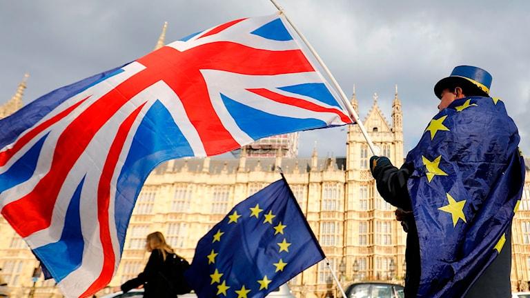 Personer håller i Europaflaggan och Englands flagga.