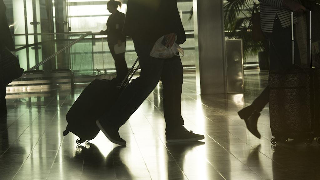 Nedre delen av kroppen på person som går med resväska i motljus inomhus.