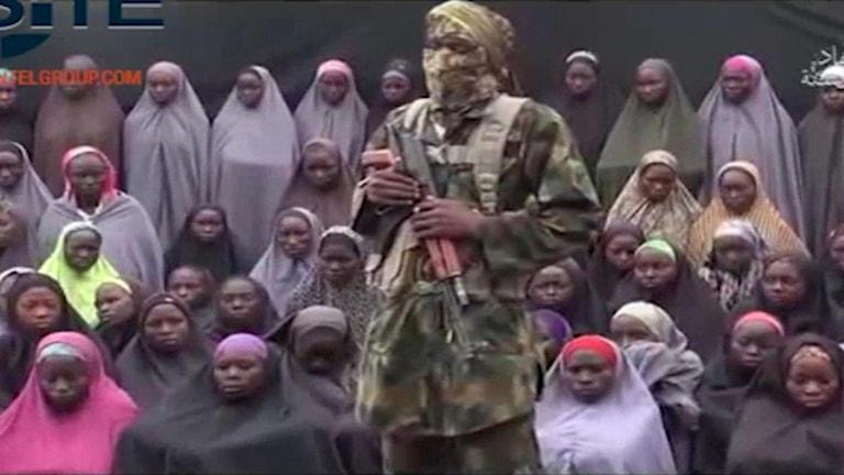Boko Haram soldat framför de flickor som kidnappades i Chibok i Nigeria 2014