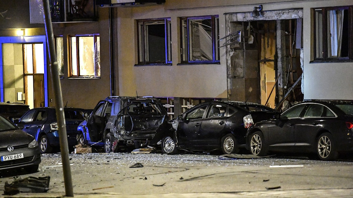 Entrén och fönstren på ett bostadshus är helt bortsprängda, bilar som står parkerade utanför har också kraftiga skador.