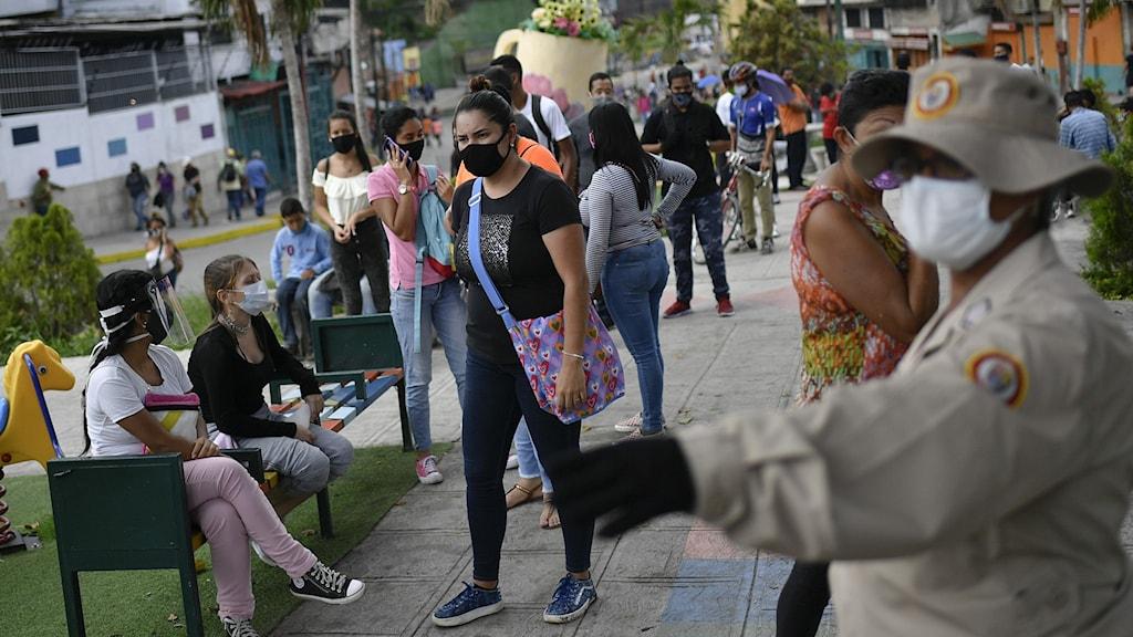 Människor med ansiktsmasker i Caracas, Venezuela.