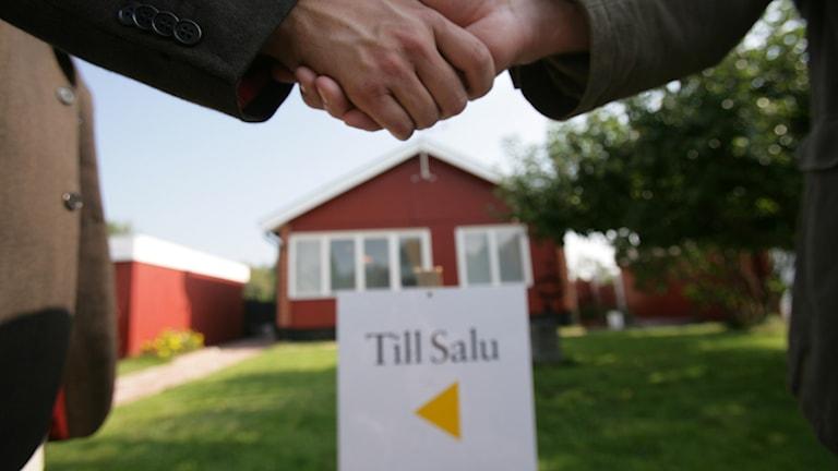 """Arrangerad bild på två personer som skakar hand vid försäljning / köp av ett bostadshus. I bakgrunden en villa med en skylt med texten """"till salu"""