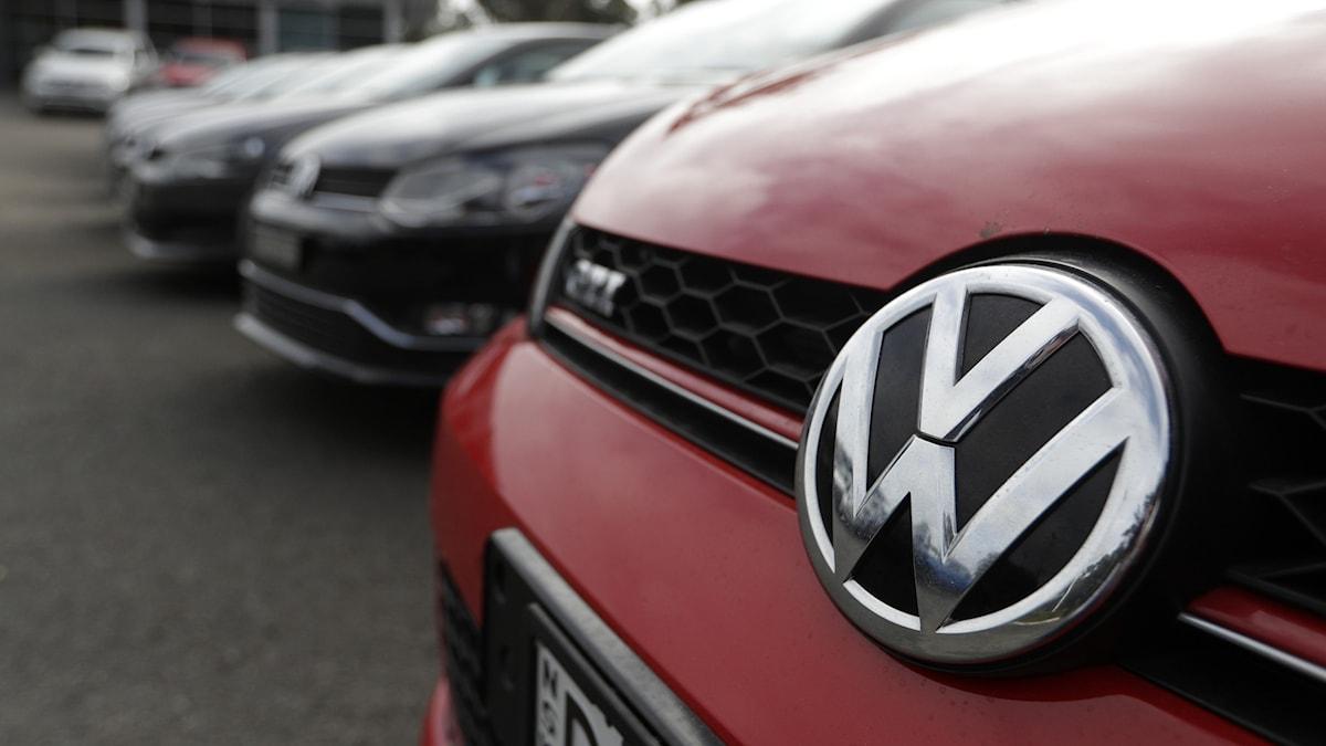 En röd Volkswagen bil står på en parkering