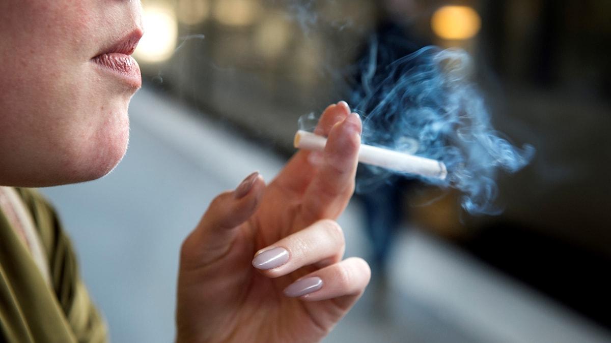Kvinna som röker en cigarett.