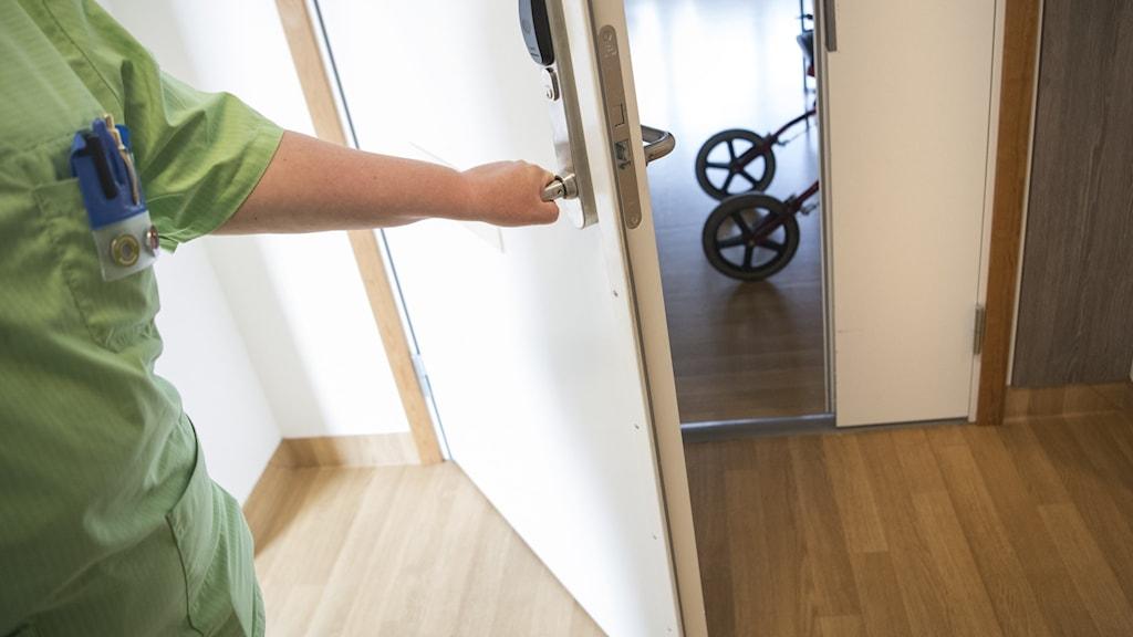 Vårdpersonal öppnar dörren till ett rum där en rullator skymtas i öppningen.