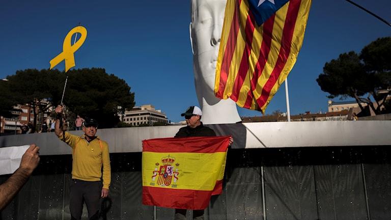 En man håller spansk flagga - kataloniens flagga syns i bakgrunden.