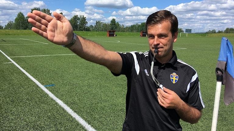 Mörkhårig fotbollsdomare med en pipa i munnen pekar med handen.