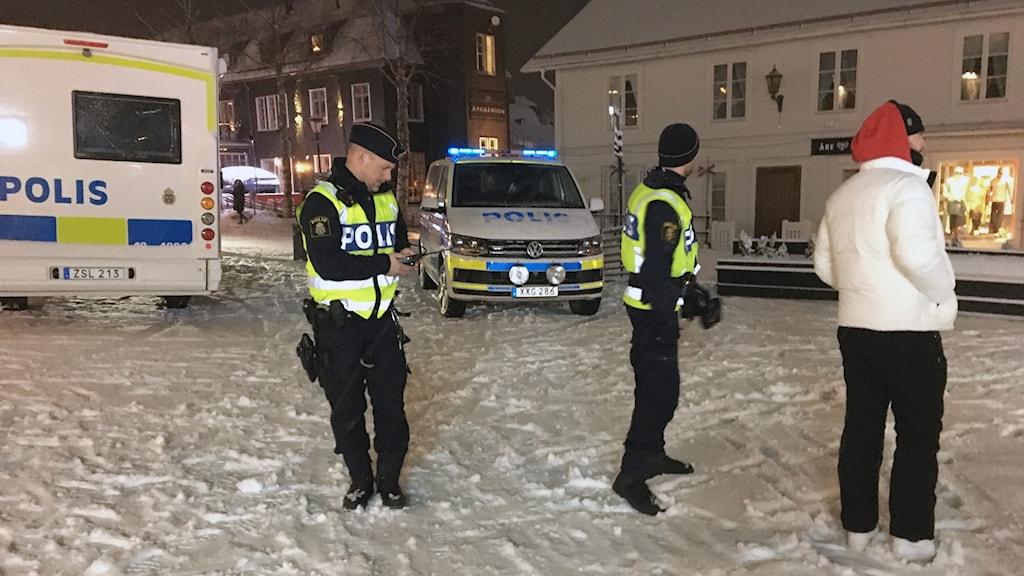 Två poliser och en ung man står på Åre torg, i bakgrunden står två polisbussar.