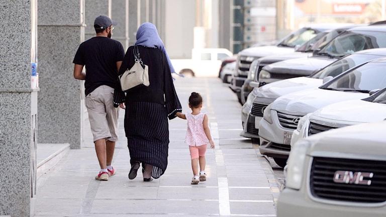 Saudisk familj går längs en gata.