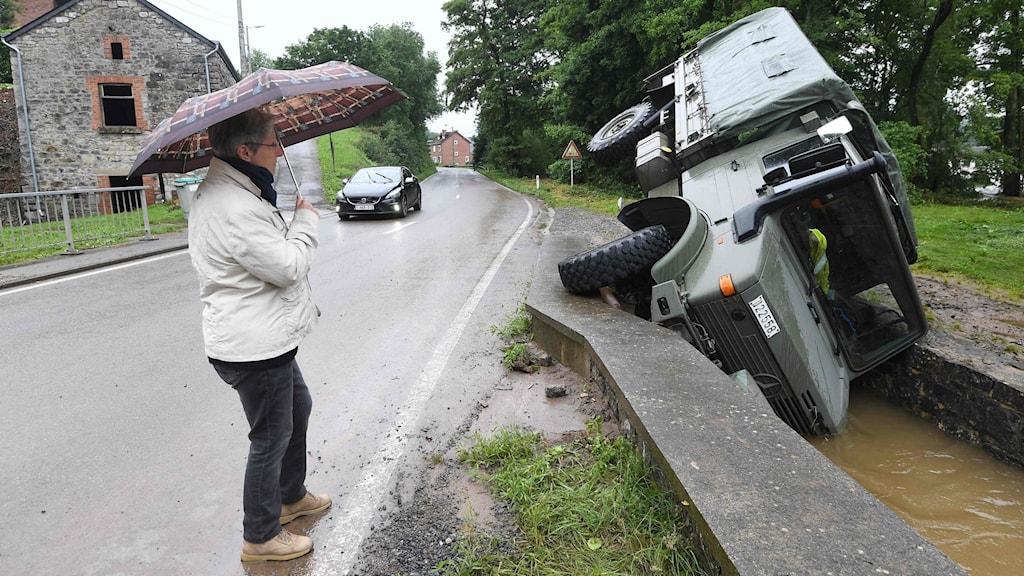 En kvinna med paraply står och tittar på en omkullvält bil