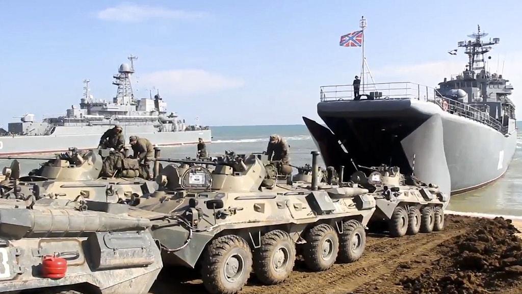 Ryska tanks kör på en militärbåt.