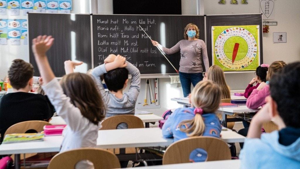en lärare på en tysk askola osm undervisar vid en tavla.