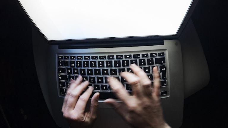 Fingrar rör sig över tangentbordet vid en upplyst dator.