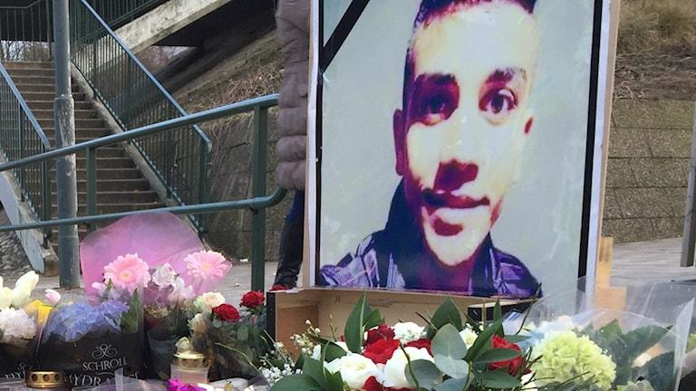Bilden visar blommor och gravljus som ställts på busshållplats Rosengård i Malmö. 16-årige Ahmed Obaid mördades i närheten den 12 januari 2017. Foto: Anna Bubenko/Sveriges Radio.