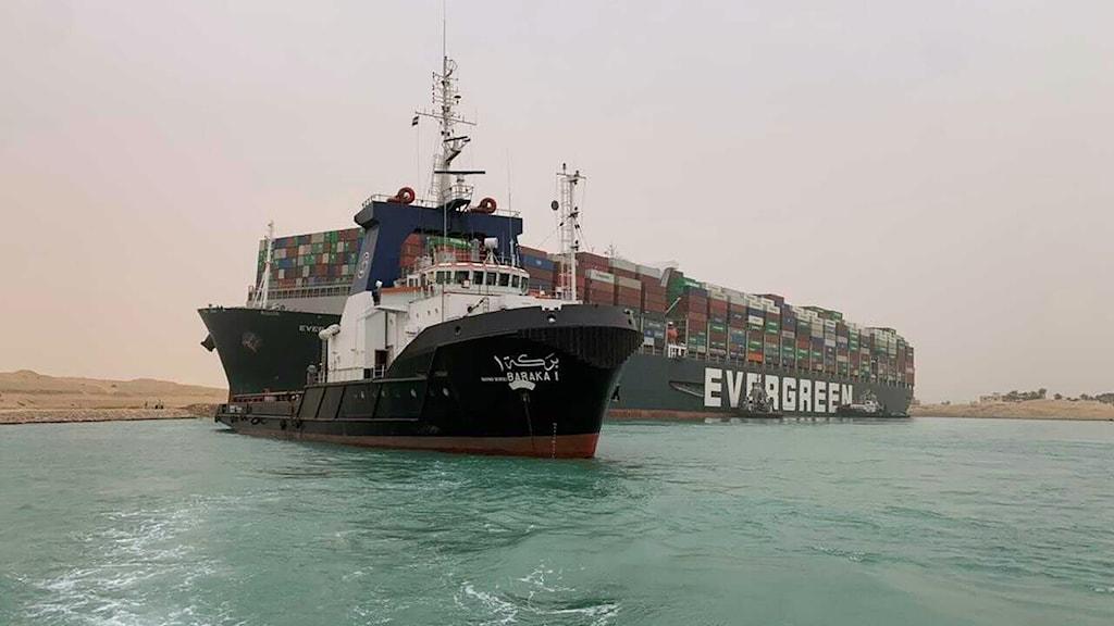 Ett mindre fartyg passerar lastfartyget Ever Green i Suezkanalen.