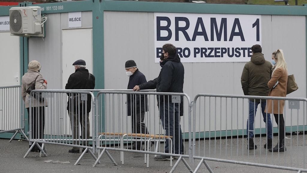 Äldre människor väntar i kö för att vaccineras mot COVID-19 på det tillfälliga sjukhuset på National Stadium i Warszawa, Polen,