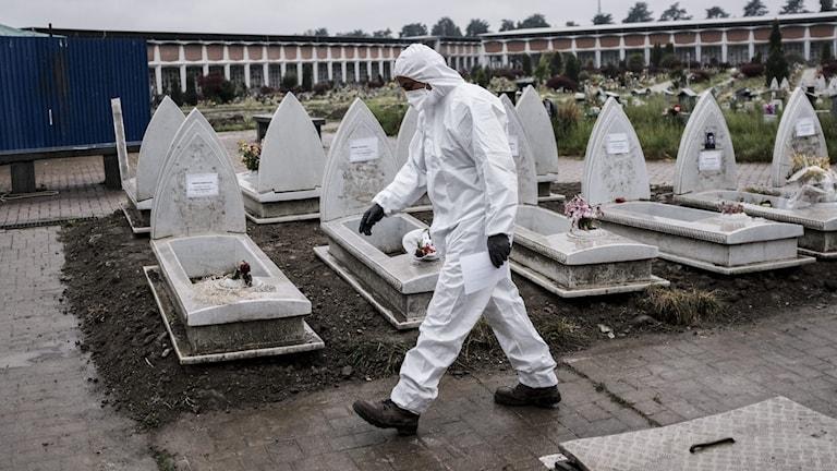man i skyddsdräkt går på kyrkogård i Italien