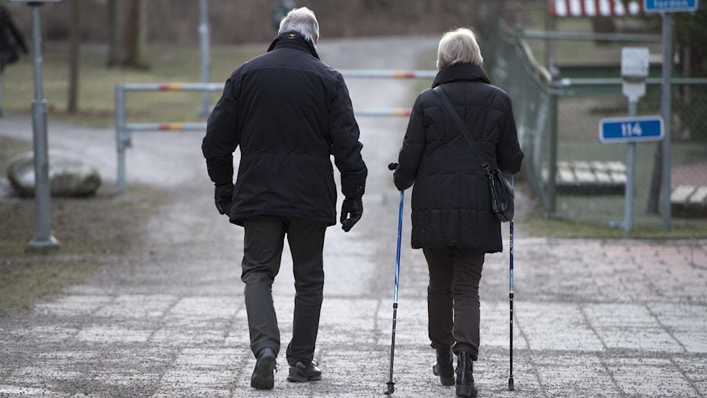 Två äldre personer går i från kameran.