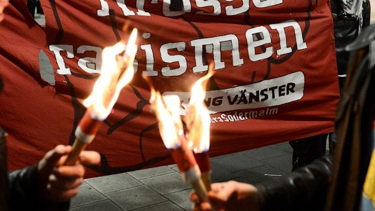 En flagga från Ung Vänster med facklor framför.