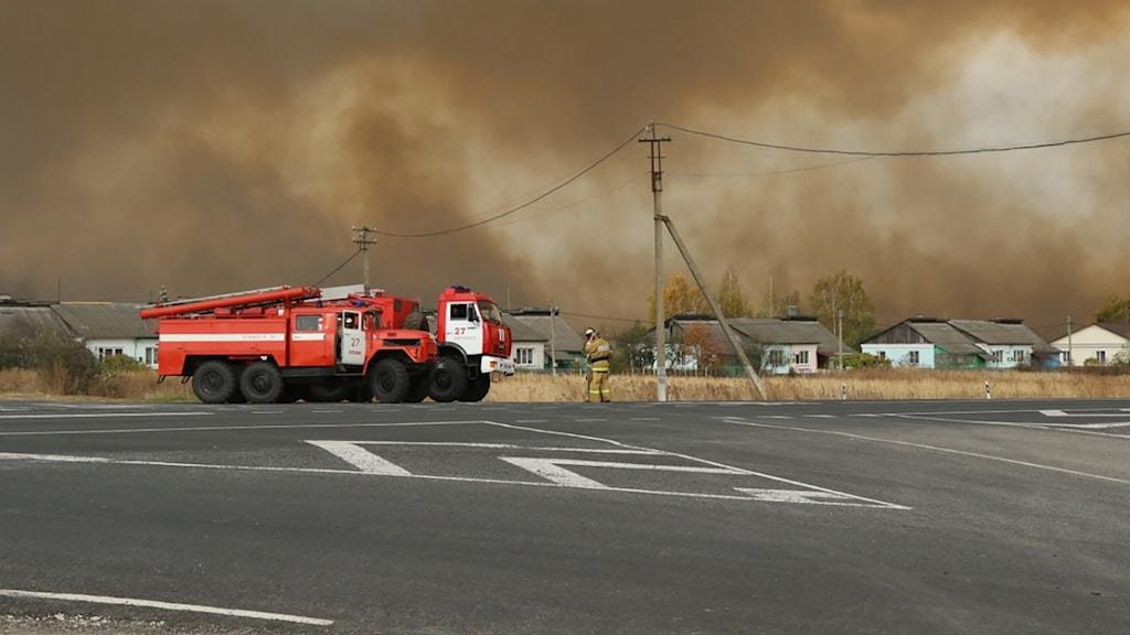 En brandbil och en brandman står på en väg, i bakgrunden syns massiv rök.